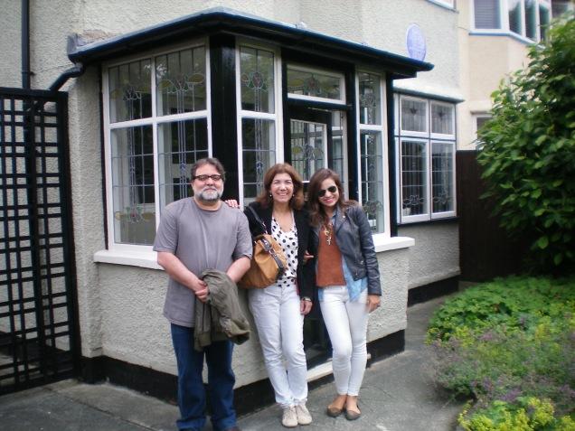 Felizes depois da visita, na frente da casa de John Lennon, com o selo azul ao fundo, indicando que morou alguém ilustre